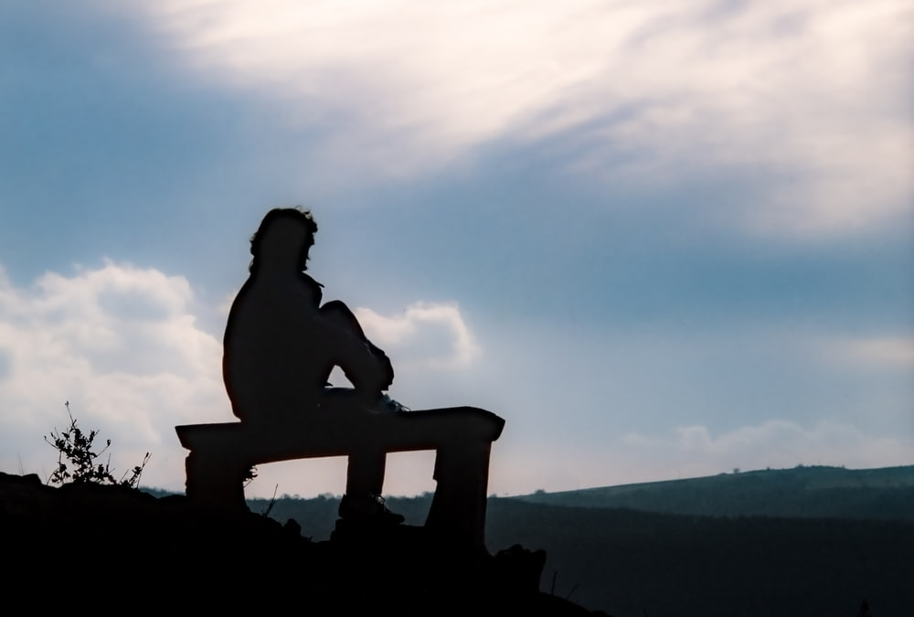 man sitting on brown wooden bench looking at the mountains during daytime