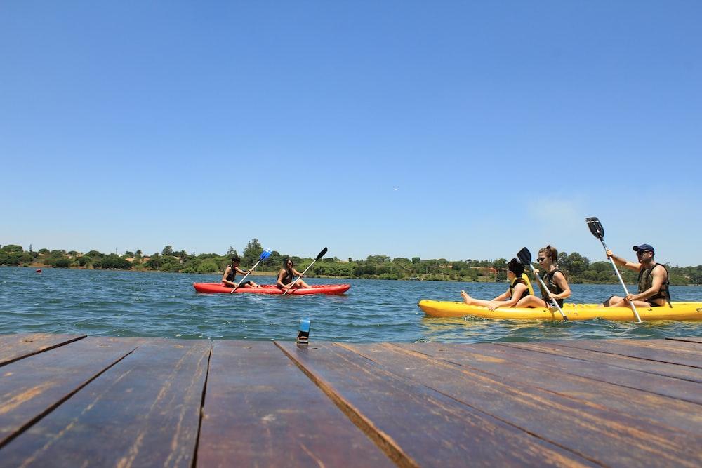people riding on red kayak on sea during daytime