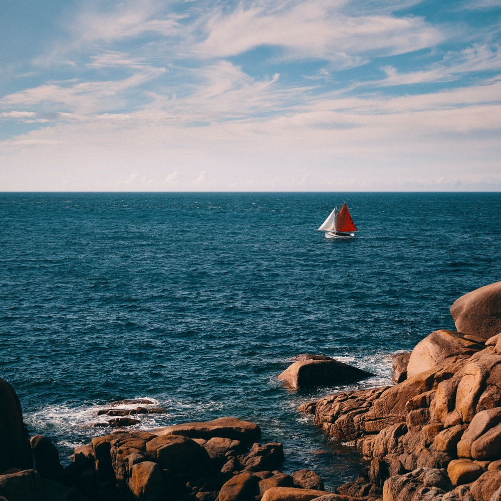 white sailboat on sea under white clouds and blue sky during daytime