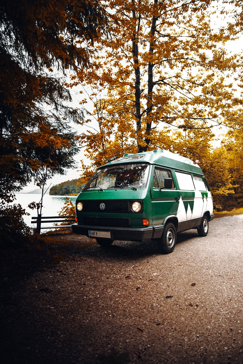 green and white volkswagen t-2 parked on the side of the road
