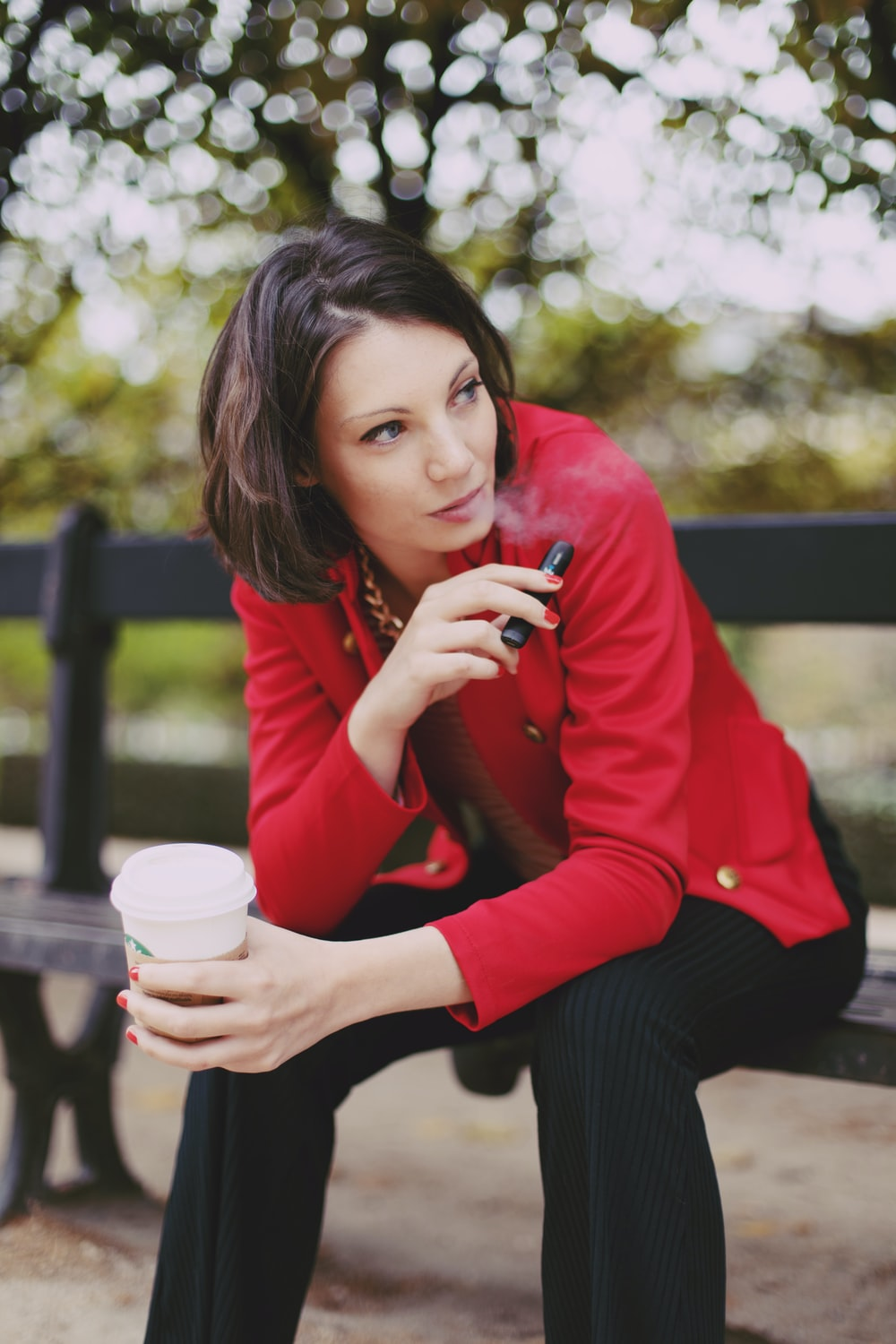 woman in red long sleeve shirt holding white disposable cup