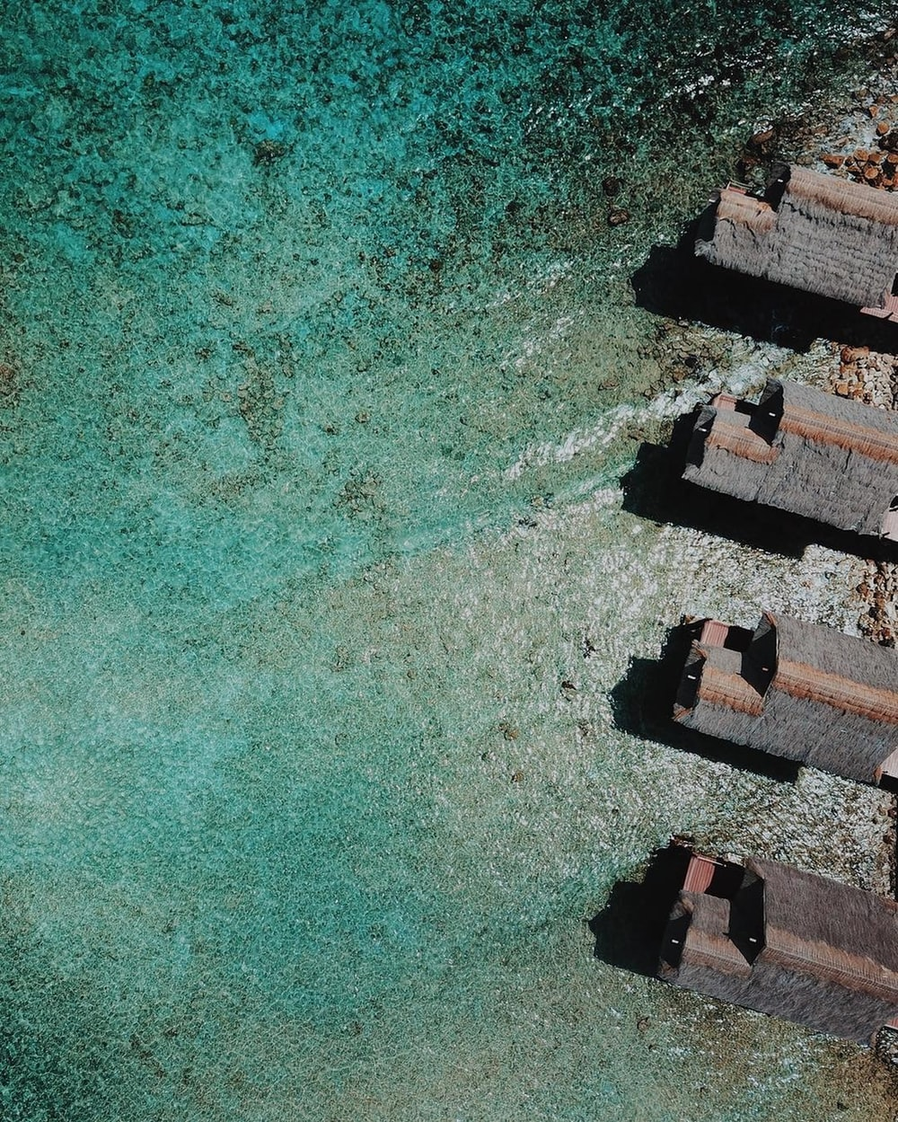aerial view of brown concrete building beside body of water during daytime