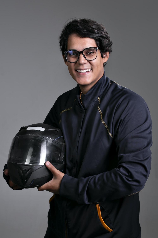 man in black dress shirt holding black helmet