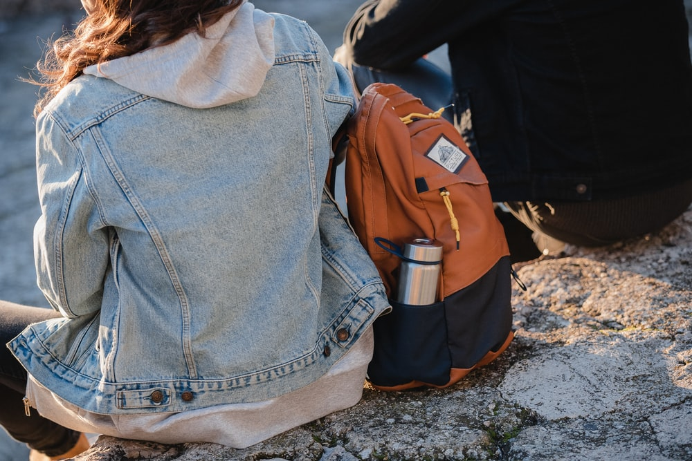 woman in blue denim jacket and brown backpack standing near brown backpack