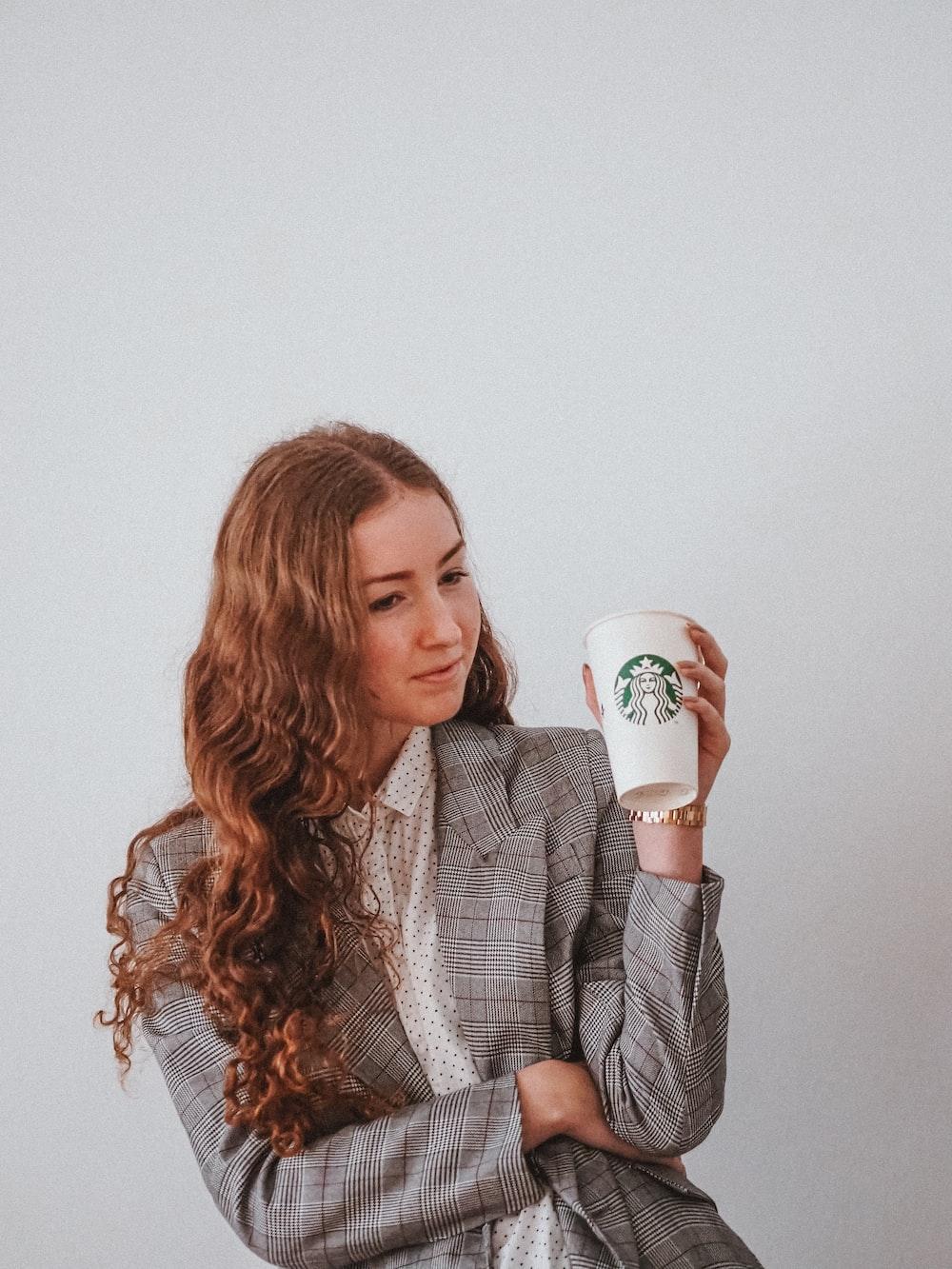 woman in gray blazer holding white ceramic mug