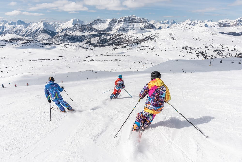 2 person in yellow jacket and blue helmet riding ski blades on snow covered mountain during