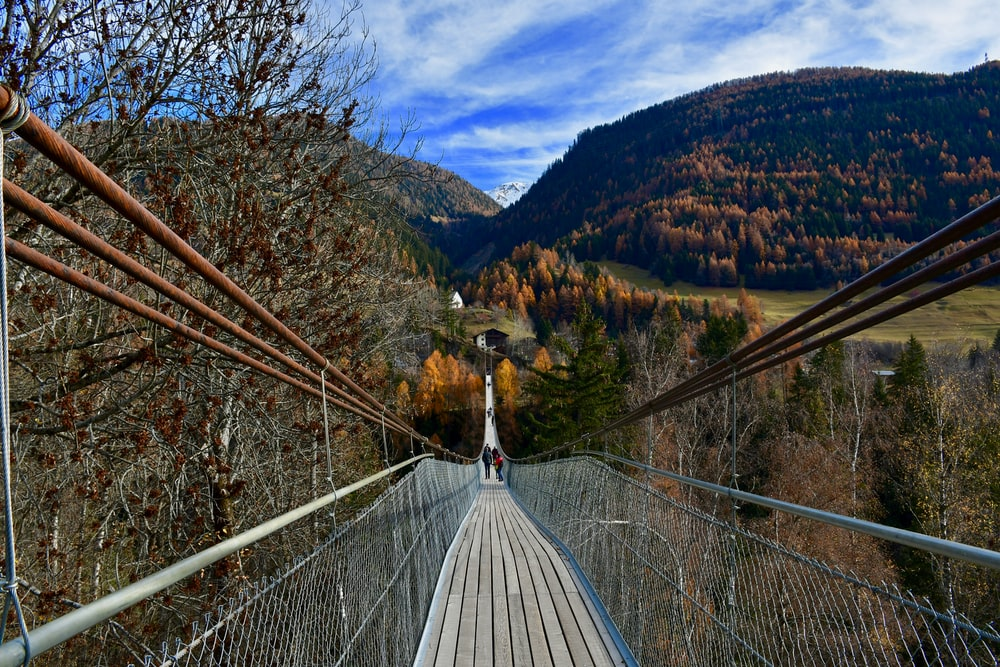 white wooden bridge over green mountains during daytime