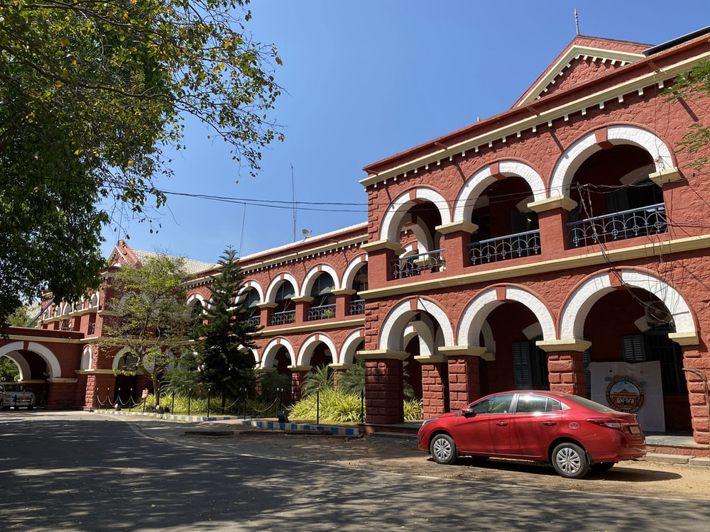 red car parked in front of brown and white concrete building during daytime