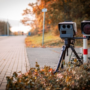 black and gray camera on tripod on road during daytime