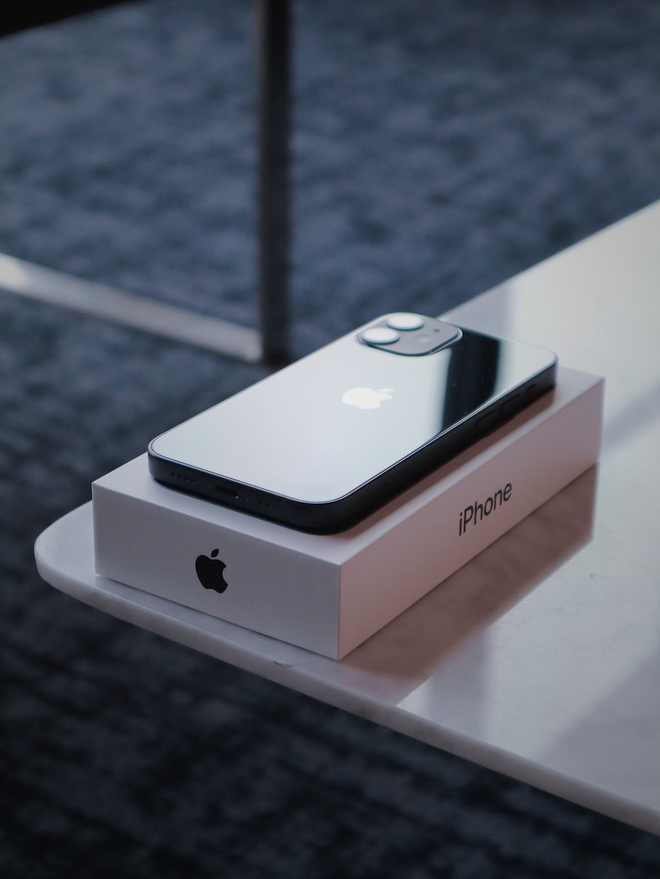 iPhone 12 mini i jego pudelku na skraju stołu