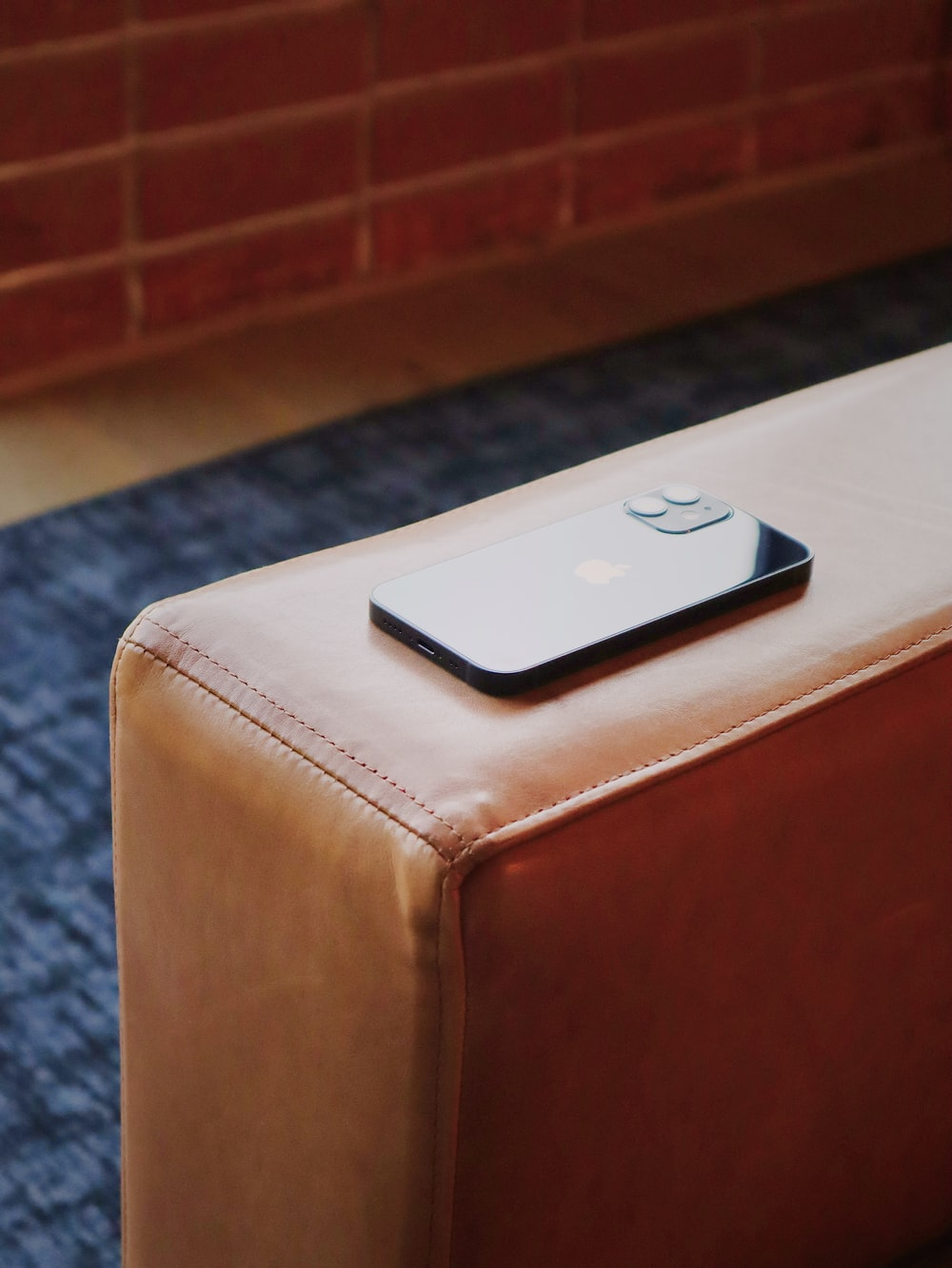 white apple remote on brown leather ottoman
