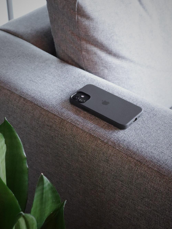 black iphone 5 on gray sofa