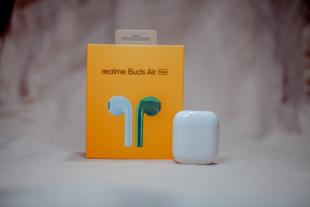 orange and white box with white apple airpods