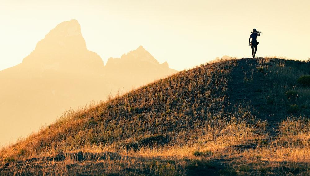 brown grass field near brown mountain during daytime