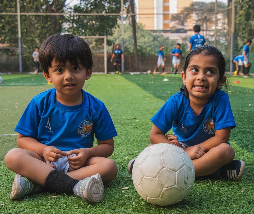 boy in blue polo shirt playing soccer during daytime