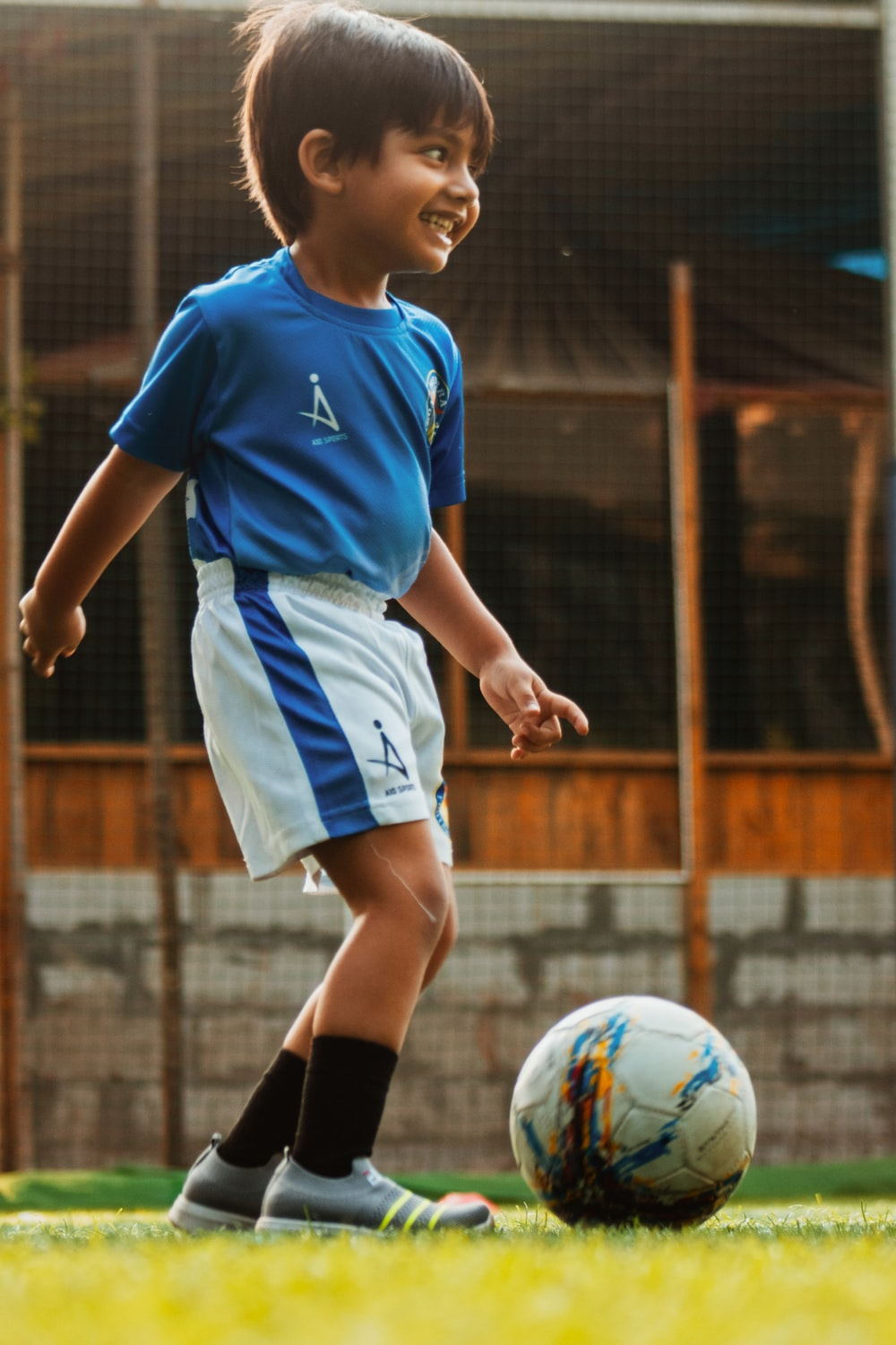 boy in blue and white soccer jersey kicking soccer ball