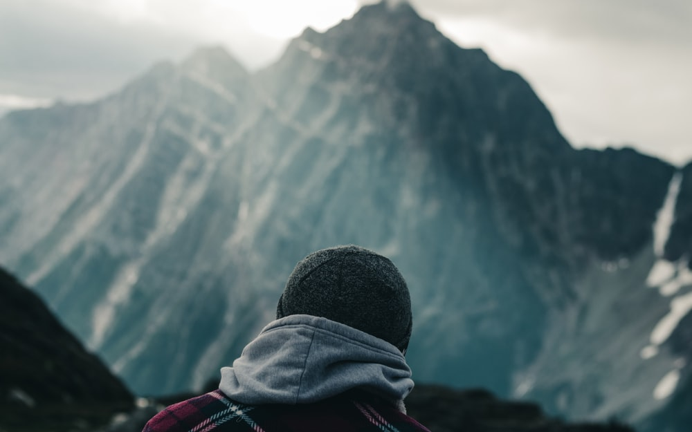 person in black knit cap and gray hoodie looking at the mountains during daytime