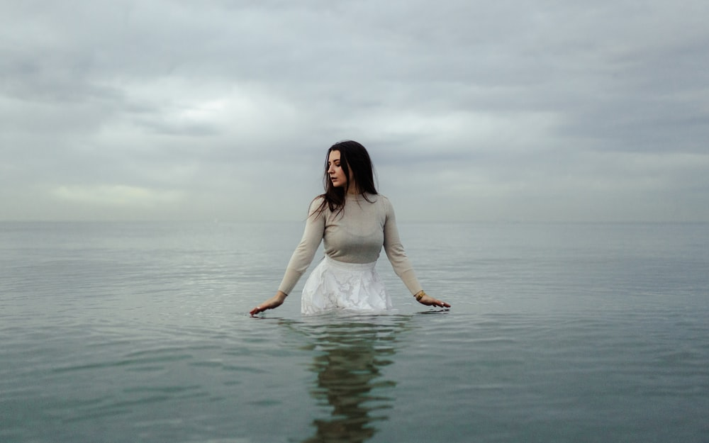 woman in white dress standing on water