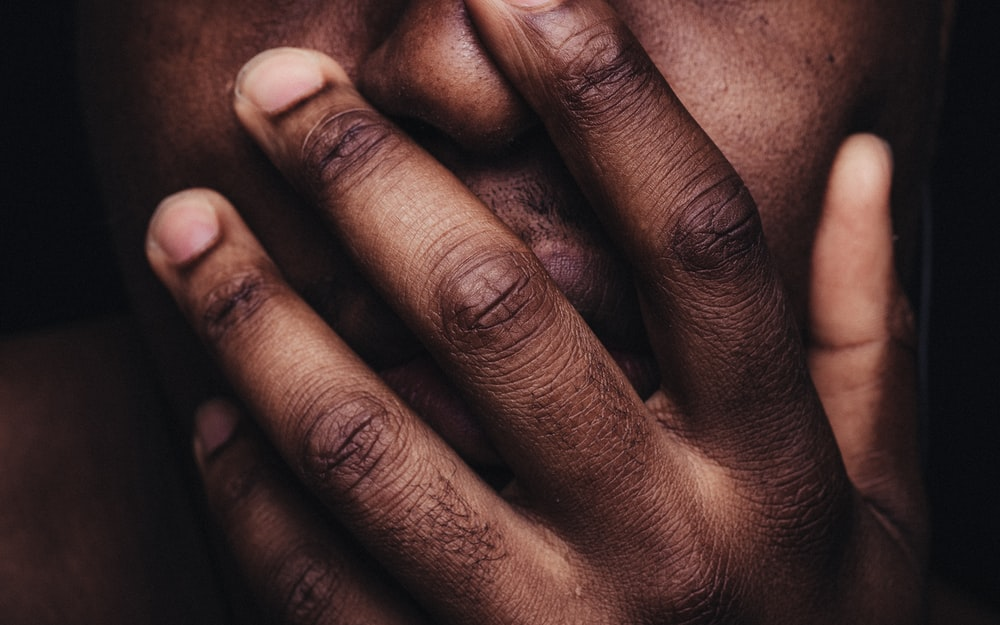persons hand on his face