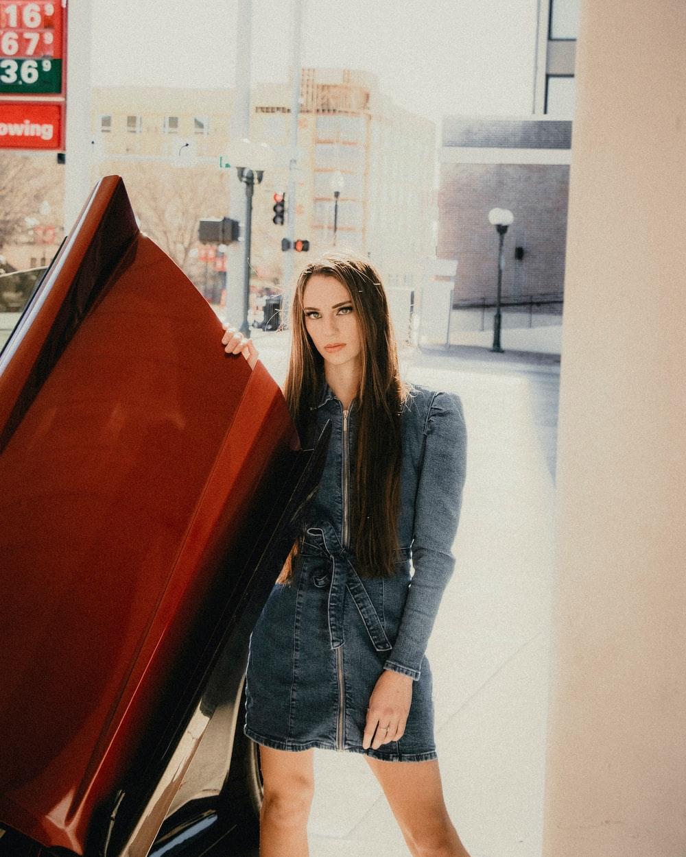 woman in blue denim jacket standing beside red car