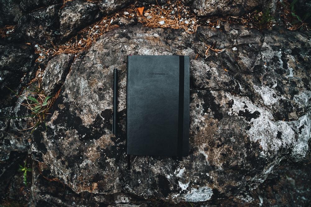 black rectangular case on rocky ground