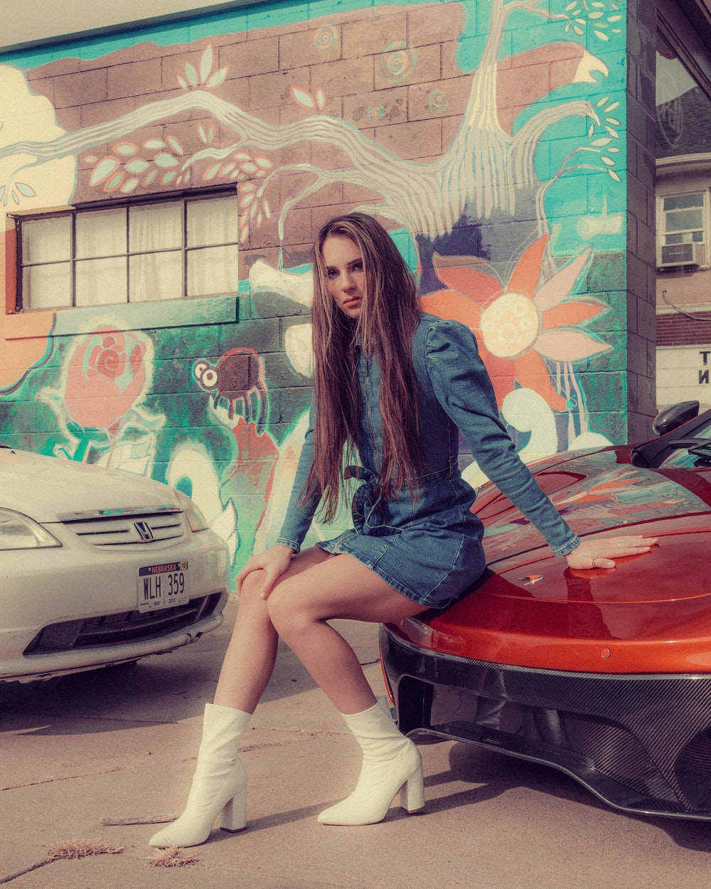 woman in blue long sleeve shirt and blue denim shorts sitting on red car
