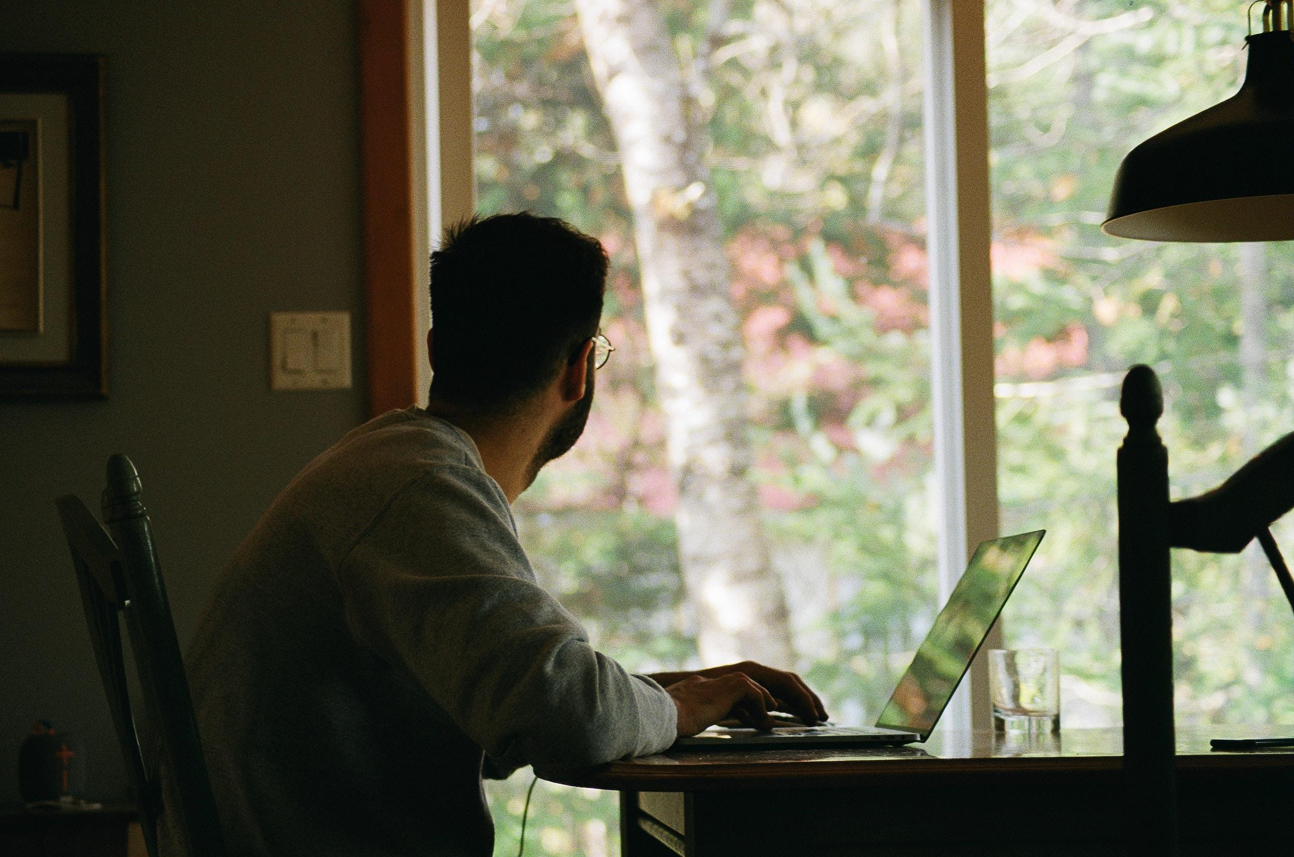 man in gray hoodie using laptop computer