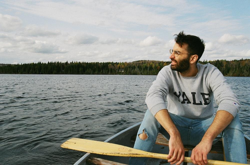 man in white crew neck t-shirt sitting on white boat during daytime
