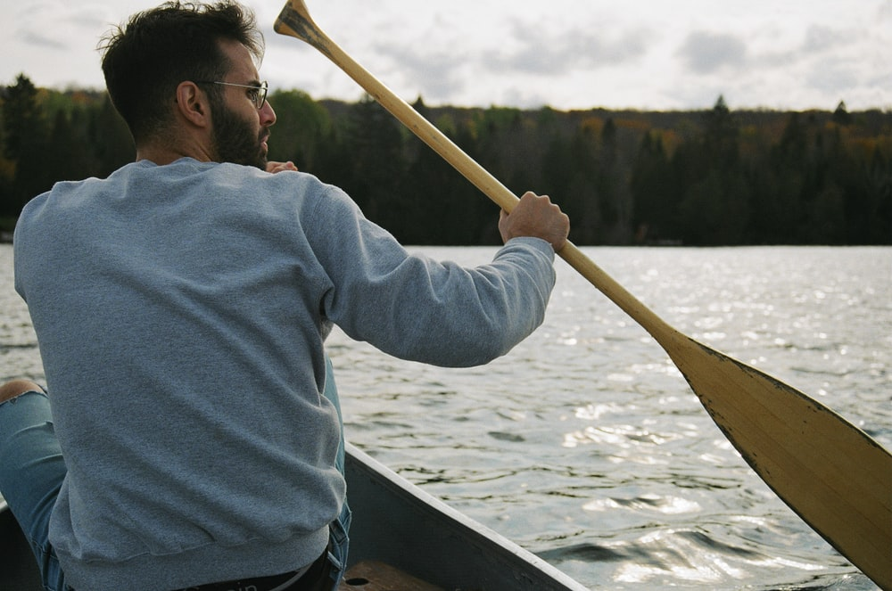 man in blue hoodie riding on boat during daytime