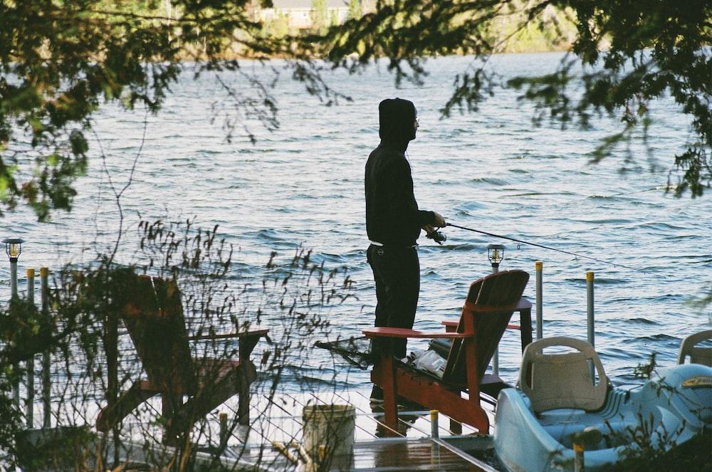 man in black jacket standing on brown wooden dock during daytime