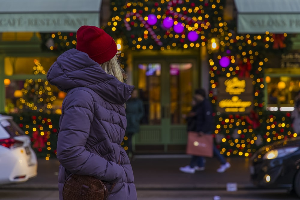 woman in red knit cap and black jacket standing on sidewalk during night time