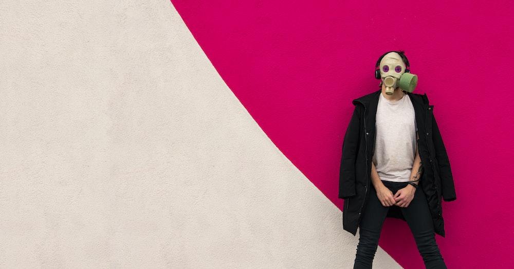 woman in black coat standing beside white wall