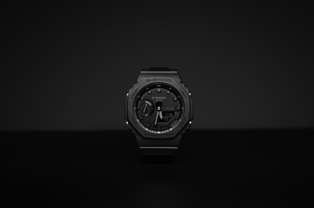 grayscale photo of round silver and black analog watch