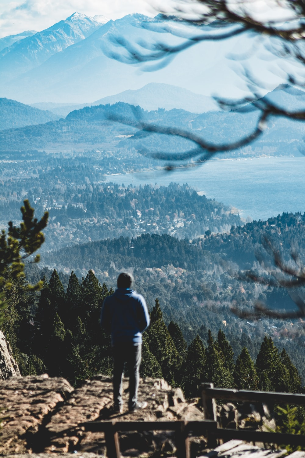 man in black jacket standing on cliff looking at the mountains during daytime