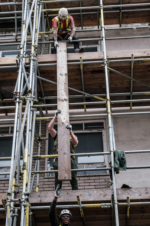 man in black shorts on brown metal ladder