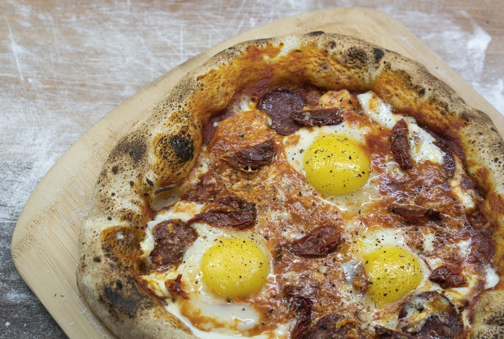 pizza with egg on white ceramic plate