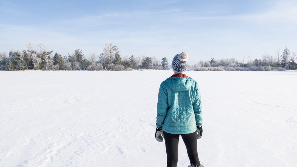 person in green jacket standing on snow covered ground during daytime