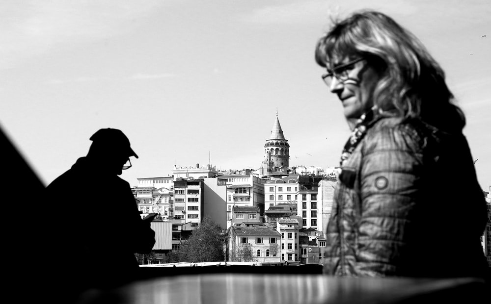 grayscale photo of woman in jacket and knit cap looking at the city