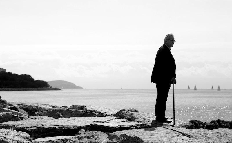 man in black coat standing on rocky shore