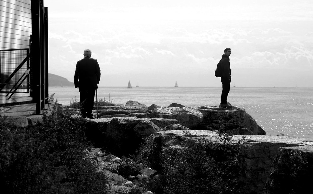 silhouette of 2 men standing on rock formation near body of water during daytime
