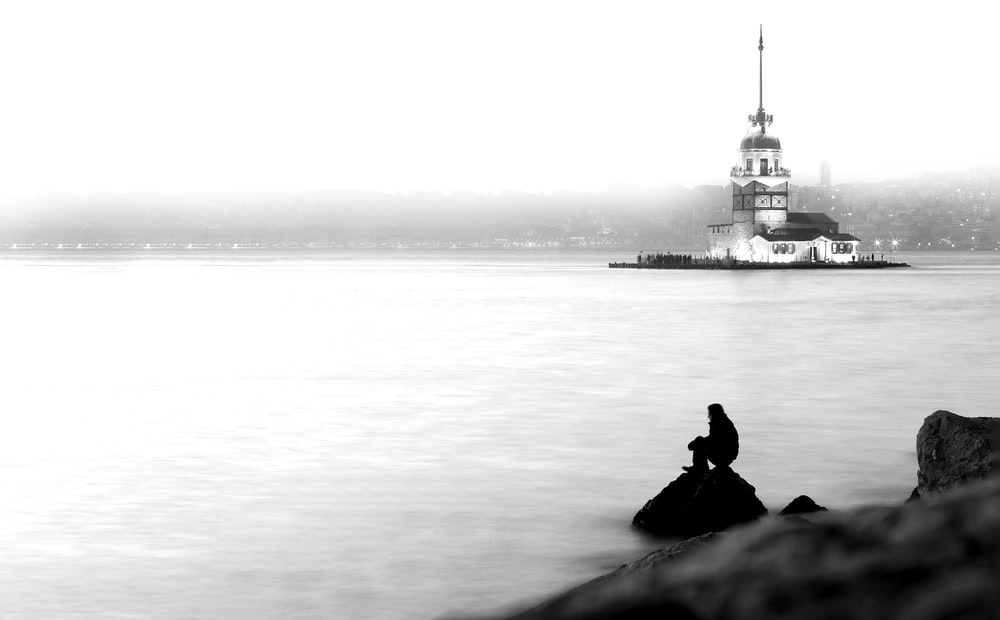grayscale photo of man sitting on rock near body of water
