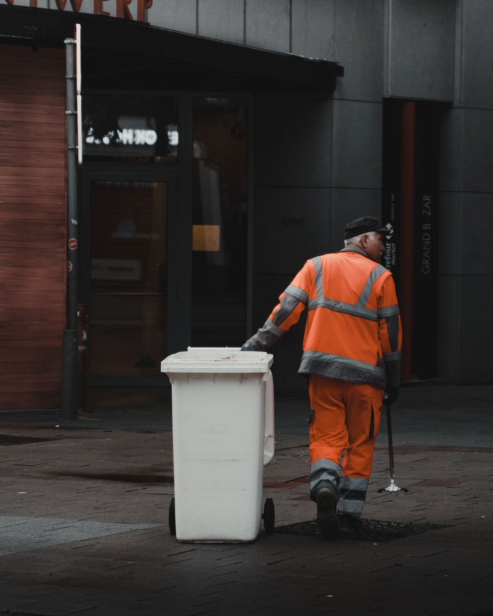 man in orange jacket and black pants standing beside white plastic trash bin