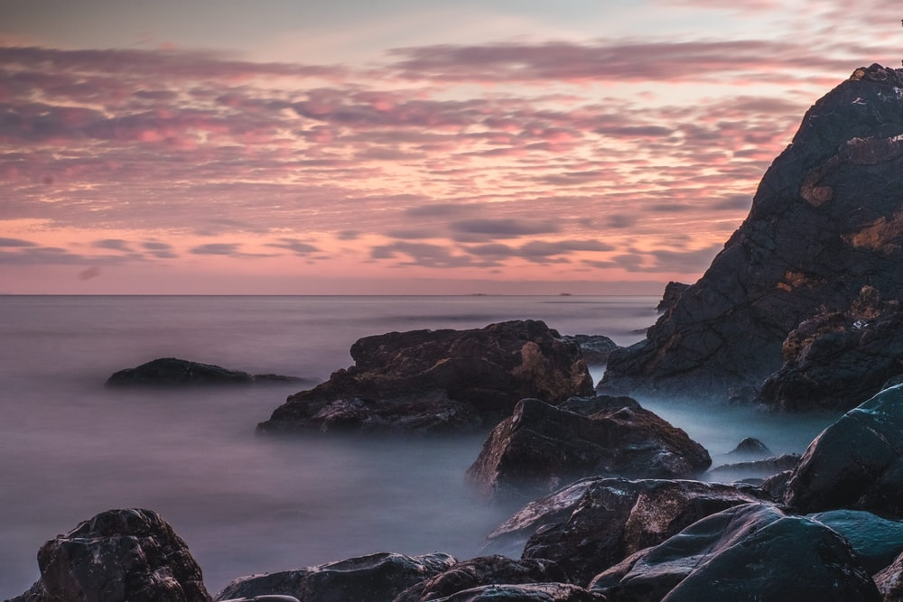 rocky shore during sunset with cloudy sky