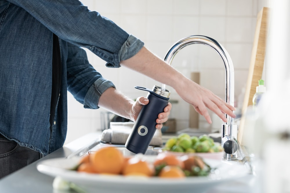 person in blue denim jacket holding stainless steel bottle