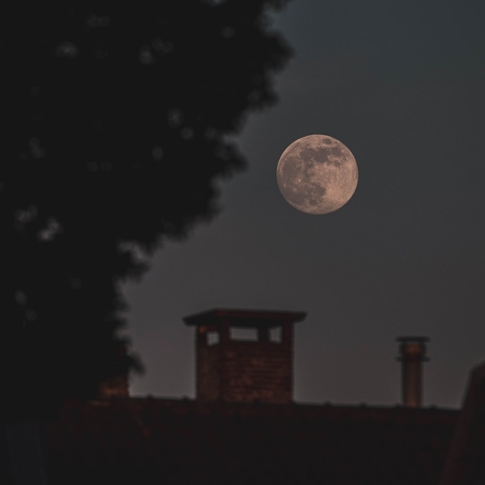 full moon over the silhouette of house