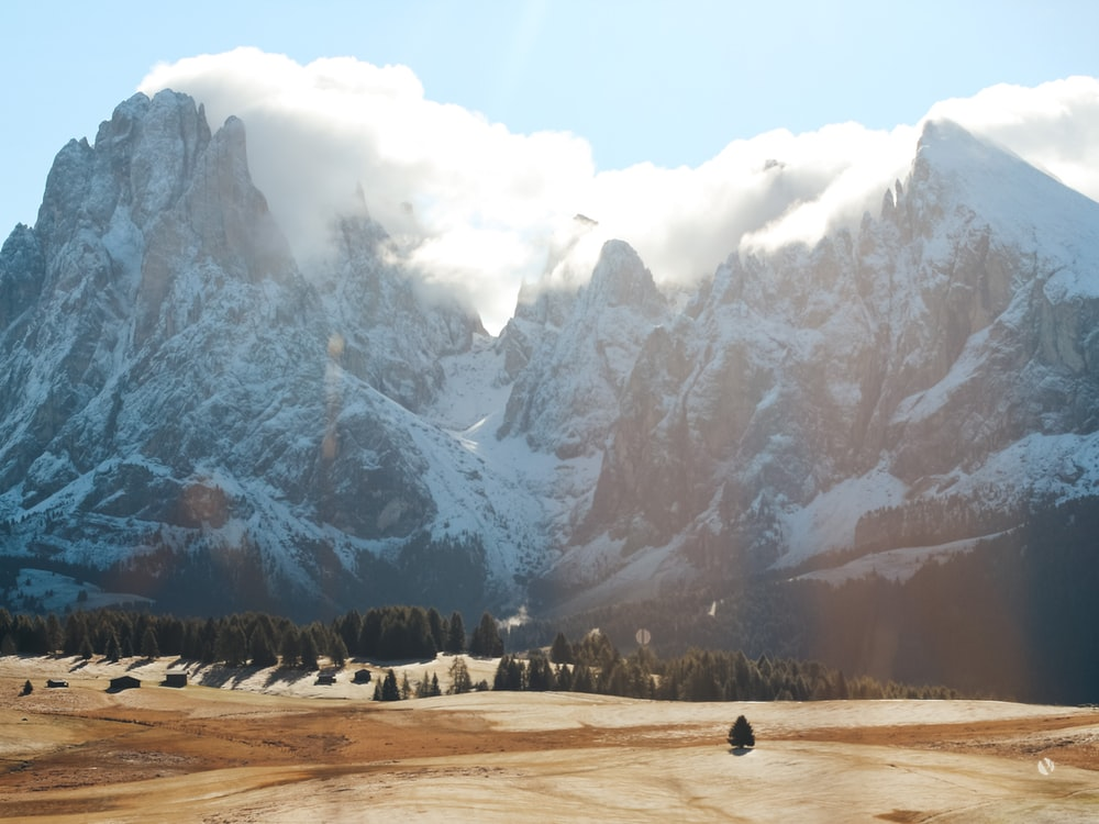 people walking on brown field near snow covered mountain during daytime