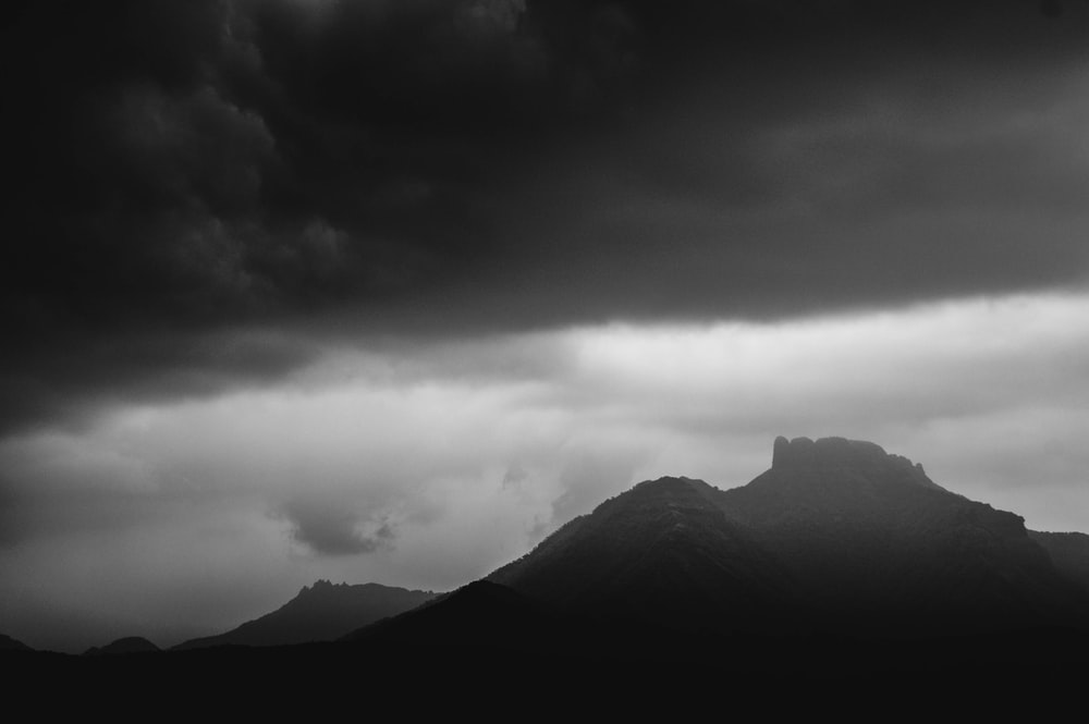 grayscale photo of mountain under cloudy sky