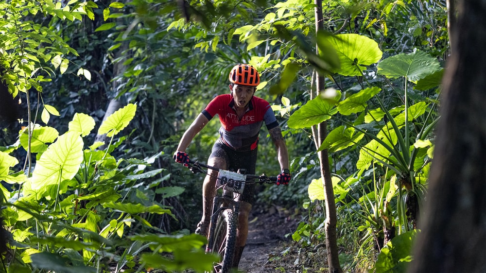 man in red and black long sleeve shirt riding on black mountain bike