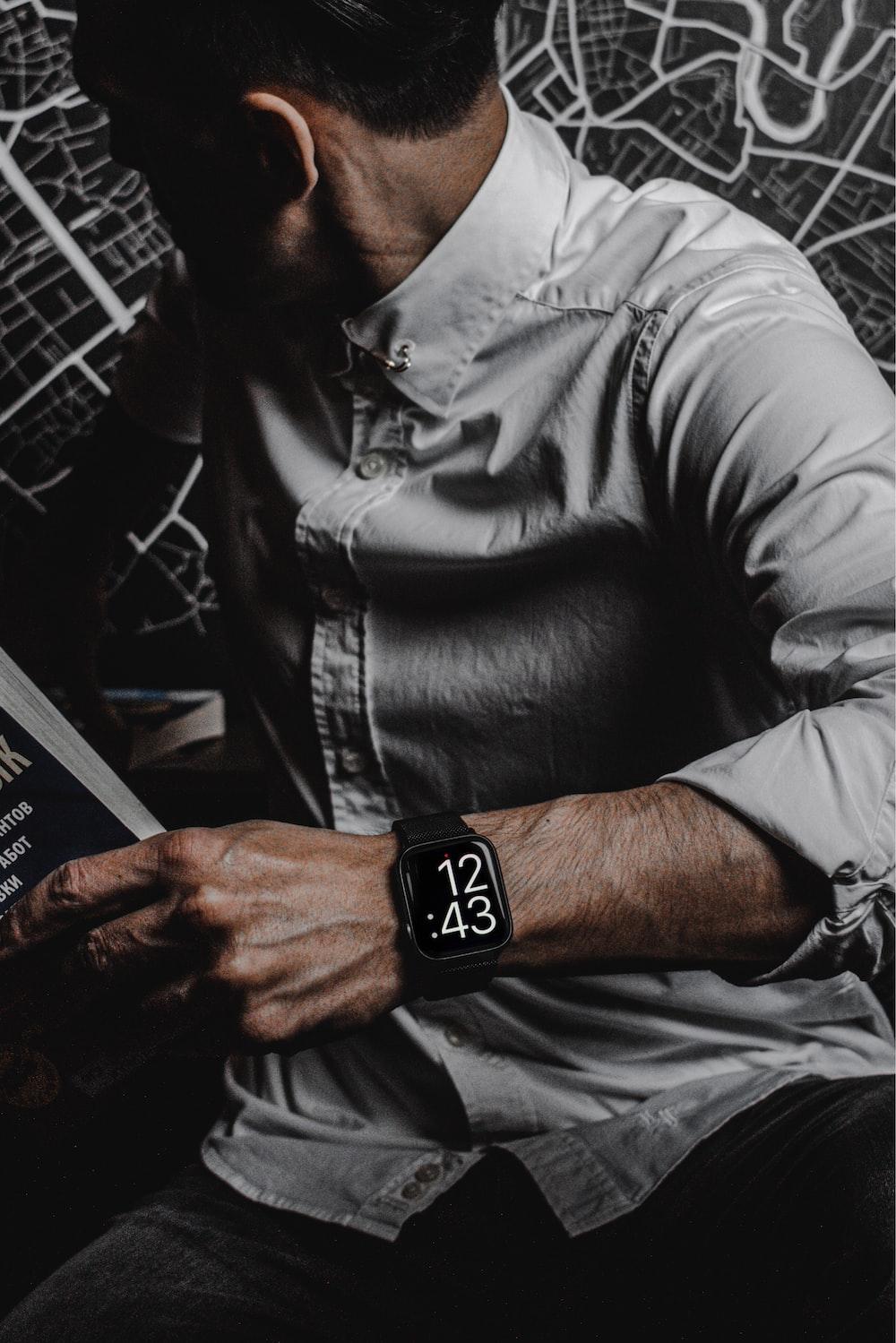 man in gray dress shirt wearing black leather strap silver round analog watch
