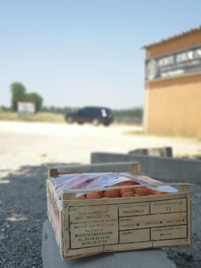 brown cardboard box on gray asphalt road during daytime